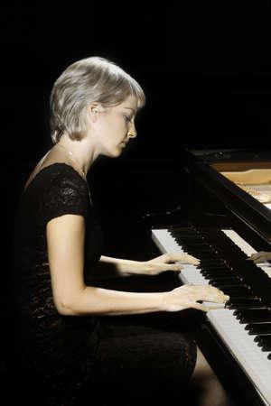 Piano player. Pianist woman playing piano. Classical musician Banco de Imagens