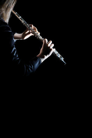 Flute instrument. Flutist hands playing flute isolated on black. Closeup of flute player