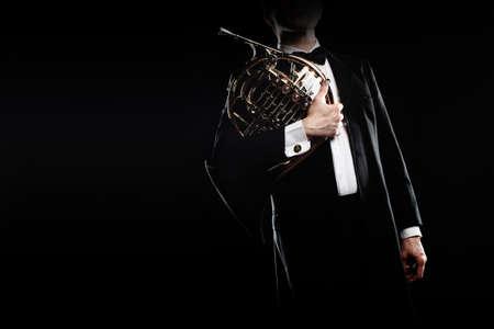 Classical musician with french horn music instrument. Elegant man hornist in tuxedo portrait. Banco de Imagens
