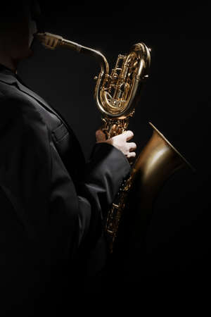 Saxophone player. Saxophonist hands playing jazz music instrument. Baritone sax player isolated Banco de Imagens