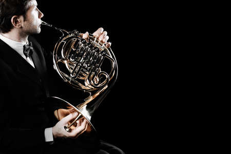 French horn player. Hornist playing brass orchestra music instrument. Classical musician
