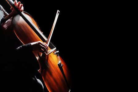 Cello player. Cellist hands playing cello with bow orchestra musical instrument closeup. Violoncello