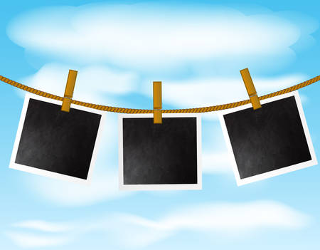 Set of blank photo frames hanging on the rope with wood pins on sky background Ilustrace