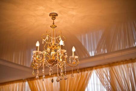Chandelier on a yellow ceiling and curtains. photo