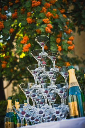 main group: Pyramid from glasses outdoors. Table with glasses for champagne, cherry in glasses.