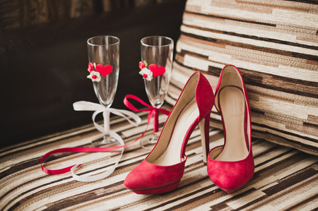no heels: Striped chair with decorated red glasses and red shoes.