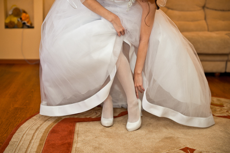 no heels: The young woman in white dresses corrects a white shoe. Stock Photo