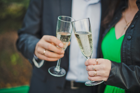 Process of a congratulation of the newly-married couple by wine drinks. photo