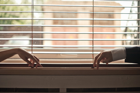 ingest: Mans and female hands on a window sill.