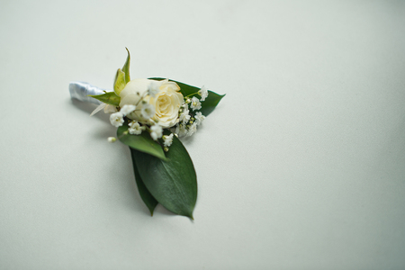 cuff link: Beautiful buttonhole from a rose and white florets.