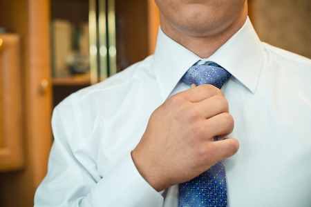 knotting: The young man fastens a tie.