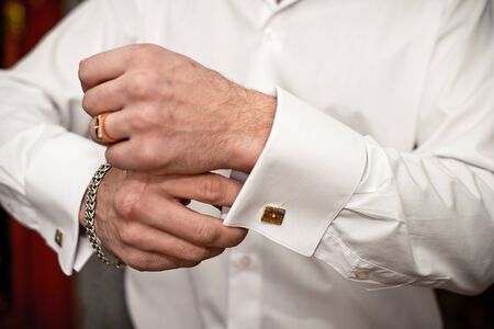 cuff links: The young man clasps a cuff link on a shirt.