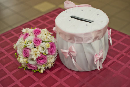 On a table there is a drum for the gifts, similar to a moneybox, and a bouquet. photo