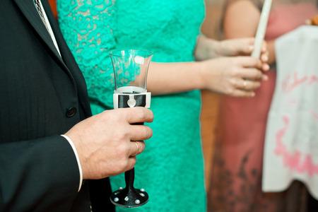 Hände mit einem Glas und einer Kerze. Standard-Bild - 32040579