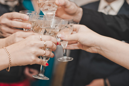 Hands of people with full glasses in movement to each other. photo
