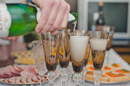 The hand pours champagne in a glass. photo