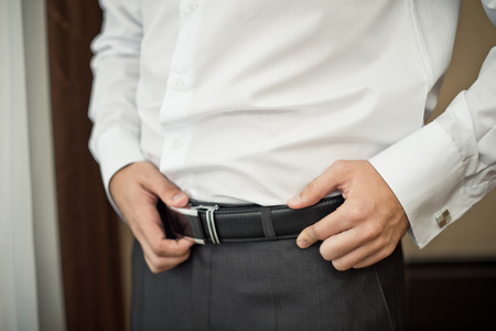 waistband: The young man corrects a belt on trousers. Stock Photo