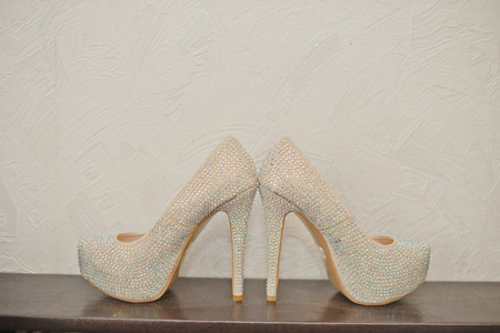 no heels: White wedding shoes stand on a table. Stock Photo