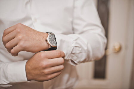 cuff link: Hands of the young man clasping a shirt.
