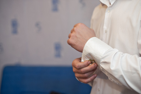 clasping: Hands of the young man clasping a shirt.