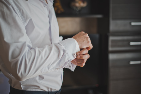 Hands of the young man clasping cuff links on shirt cuffs. Stock Photo