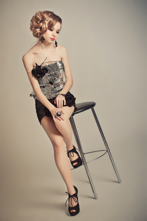 Advertising of ornaments and accessories, the photo of the girl on a grey background to the utmost.