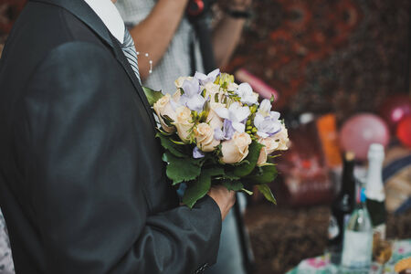 The groom has control over a bunch of flowers. photo