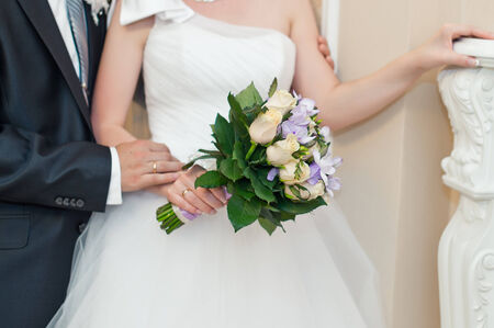 The bride has control over a bunch of flowers. photo