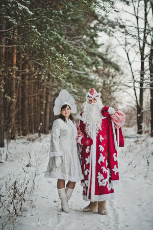 grandfather frost: The granddaughter the Snow Maiden and the Grandfather Frost in the winter wood. Stock Photo