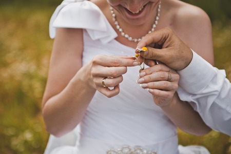 newly wedded couple: Hands of the newly-married couple hold wedding rings.