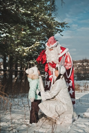 snegurochka: Santa Claus hands over gifts to the child.