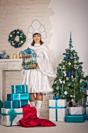 kokoshnik: Portrait of the beautiful girl in the New Years dress with gifts.