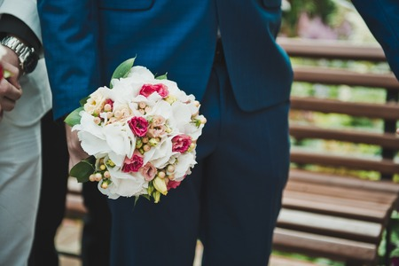 The man keeps a bouquet in a suit.