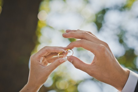 marriage ceremonies: Palms of the newly-married couple with wedding rings in fingers. Stock Photo