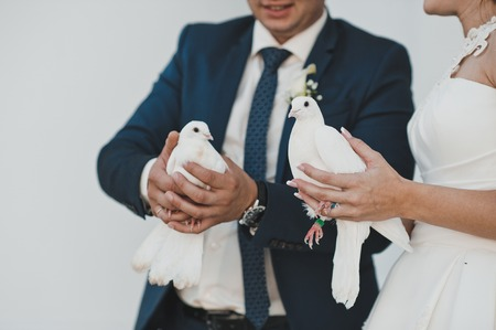 Newly-married couple holds pigeons.