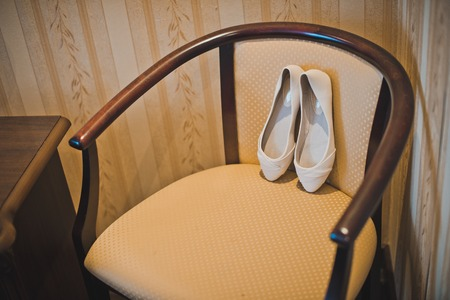 White shoes on a beige chair. photo