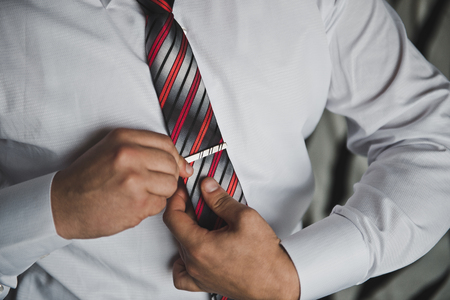 fastens: The man fastens a tie.
