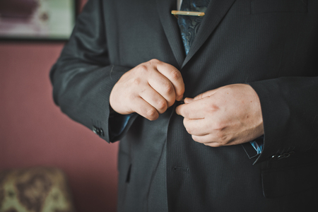 suit  cuff: The man clasps a jacket button.