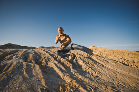 somersault: The man jumps on sandy barkhans at sunset.
