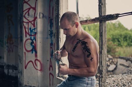 brawny: The brawny young man tears chains.