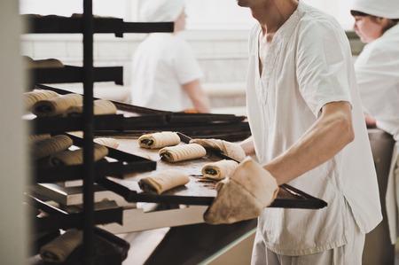 haciendo pan: Un trabajador lleva una bandeja de pan.