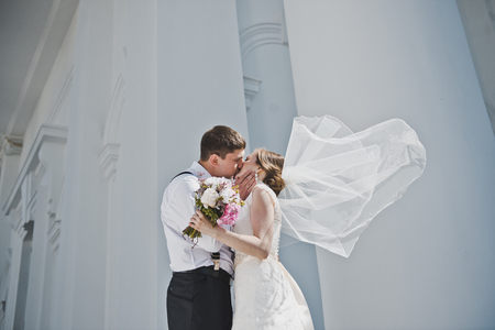 Kiss men and women on the background of the white Church.