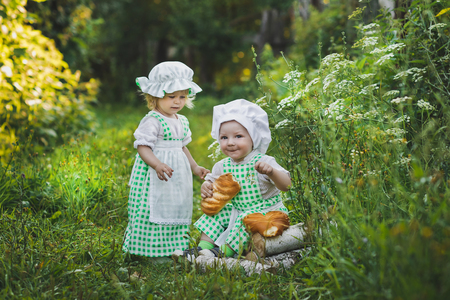 children clothing: Children clothing bakers walking in the garden. Stock Photo