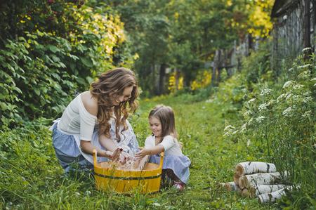 lavando ropa: ropa de la mamá y la hija de lavado en una cuenca.
