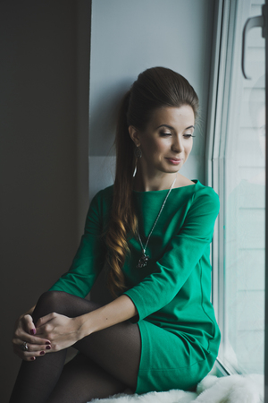 slash: A girl with long brown slash on the windowsill.