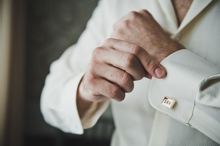cuff link: Putting on the clasps on the sleeve of a shirt. Stock Photo