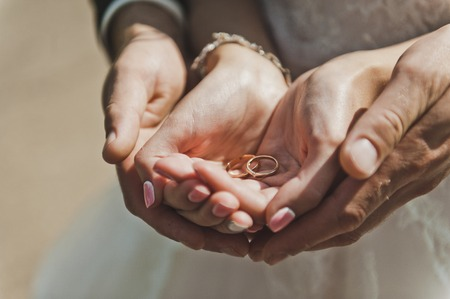 Male and female hands holding wedding rings. Archivio Fotografico