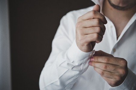 cufflink: The process of dressing the shirt of the man.