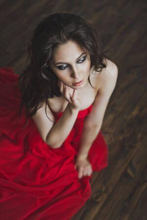 zenith: Girl in open dress sitting on the floor. Stock Photo