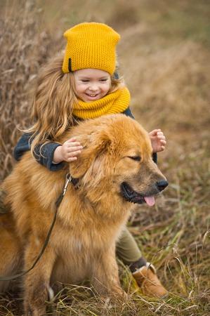 Little girl in a yellow hat and scarf, stroking the face of a huge red dog. 스톡 콘텐츠